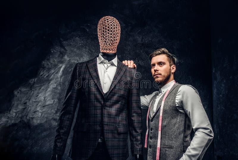 Un jeune couturier sûr posant à côté d'un mannequin dans le costume des hommes faits sur commande exclusifs dans un tailleur fonc photo libre de droits