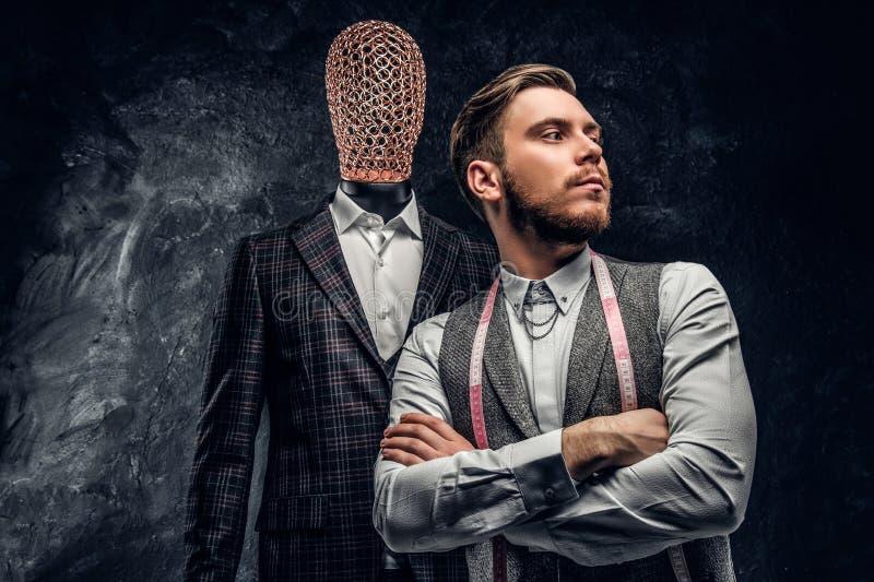 Un jeune couturier sûr posant à côté d'un mannequin dans le costume des hommes faits sur commande exclusifs dans un tailleur fonc images stock