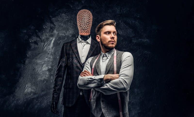 Un jeune couturier sûr posant à côté d'un mannequin dans le costume des hommes faits sur commande exclusifs dans un tailleur fonc image libre de droits