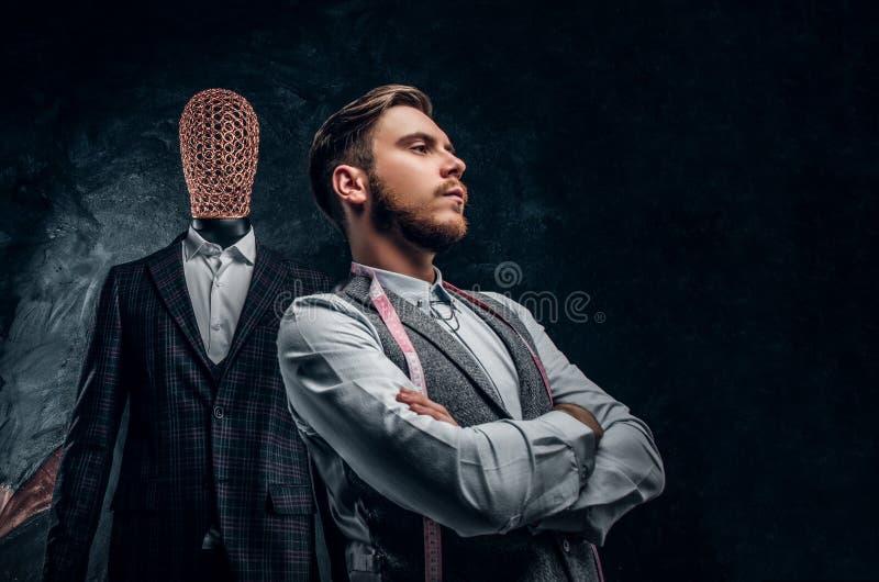 Un jeune couturier sûr posant à côté d'un mannequin dans le costume des hommes faits sur commande exclusifs dans un tailleur fonc photographie stock