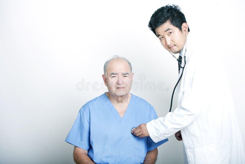 Un jeune docteur asiatique soulageant un patient adulte supérieur images libres de droits