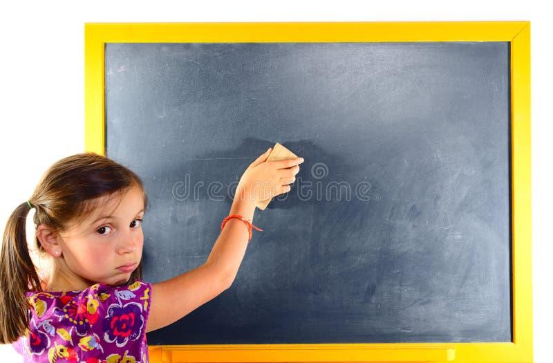 Un jeune effacement d'écolière le tableau noir photo stock