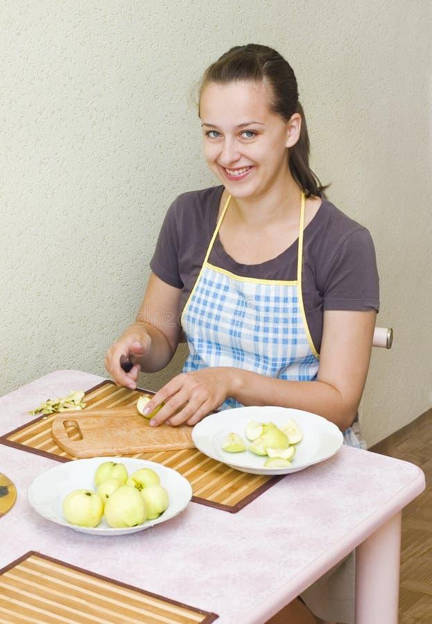 Un jeune femme coupe les pommes images stock