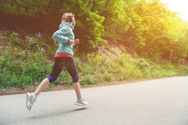 Un jeune fonctionnement blond de femme pratique dehors en parc de montagne de ville dans les rayons chauds de forêt par image libre de droits