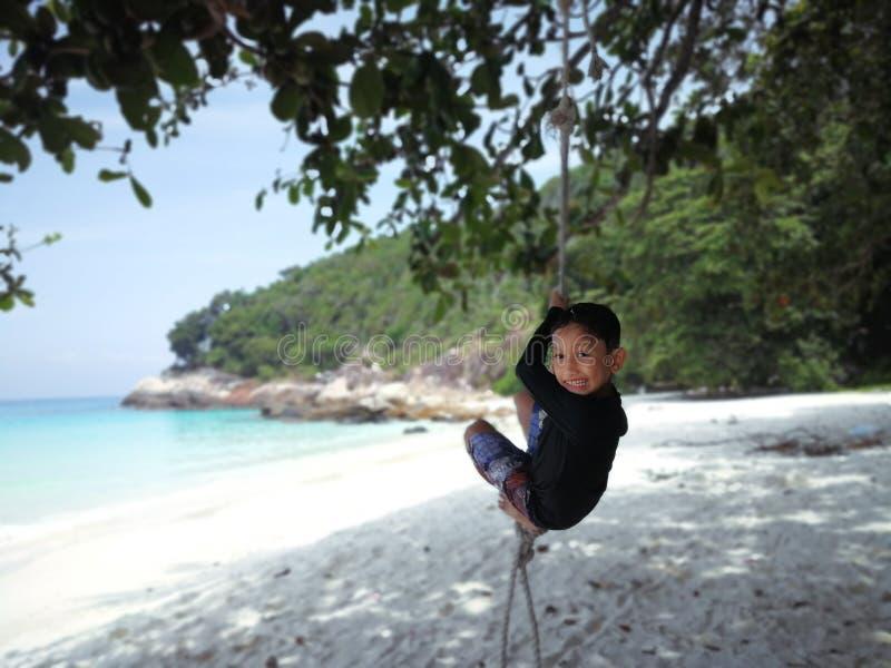 Un jeune garçon accroche à la corde par la plage photos libres de droits