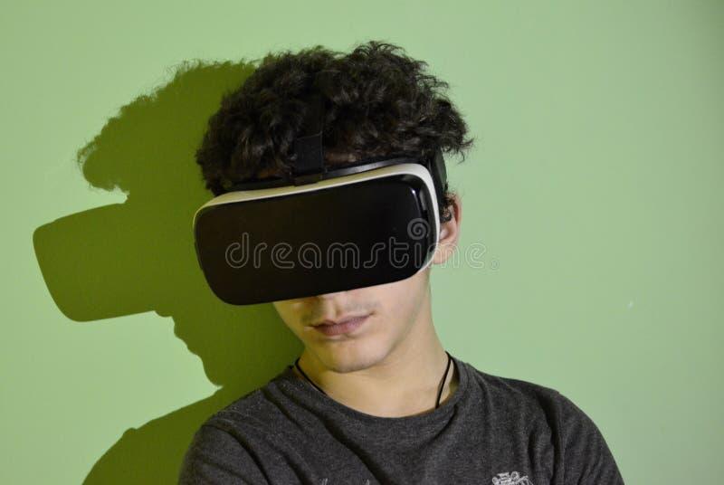 Un jeune garçon caucasien porte la visionneuse de VR 360 dans sa chambre photo stock