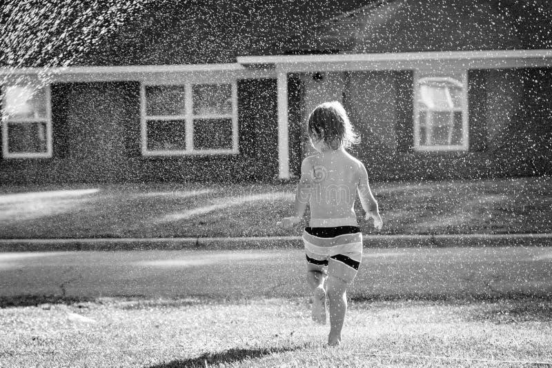 Un jeune garçon courant par une arroseuse dans la cour photos stock