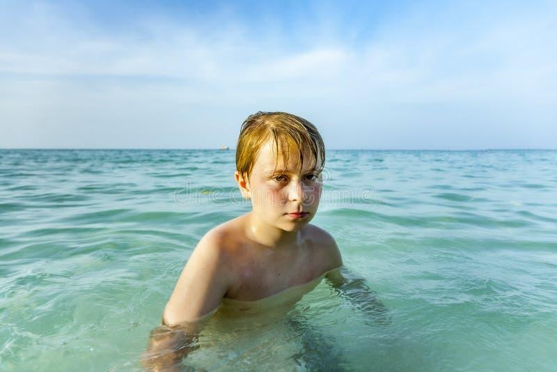 Un jeune garçon en colère traverse l'eau salée claire et chaude photo libre de droits