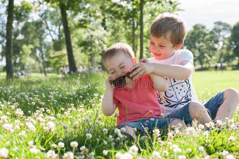 Un jeune garçon et un petit enfant en bas âge jouant en été f images libres de droits