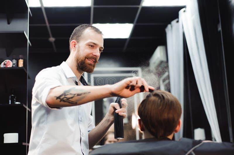 Un jeune garçon mignon obtenant une coupe de cheveux images libres de droits