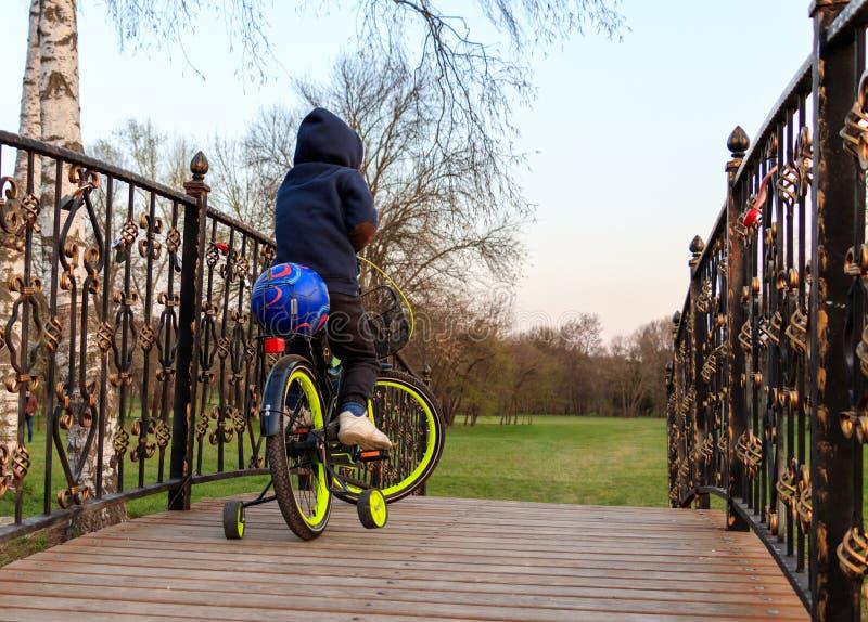 Un jeune garçon monte une bicyclette au-dessus d'un pont en bois photographie stock