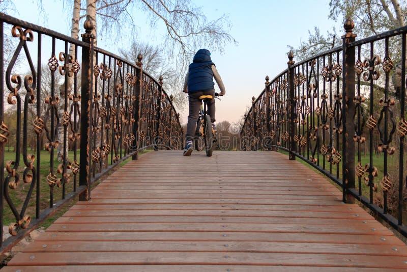 Un jeune garçon monte une bicyclette au-dessus d'un pont en bois photos libres de droits