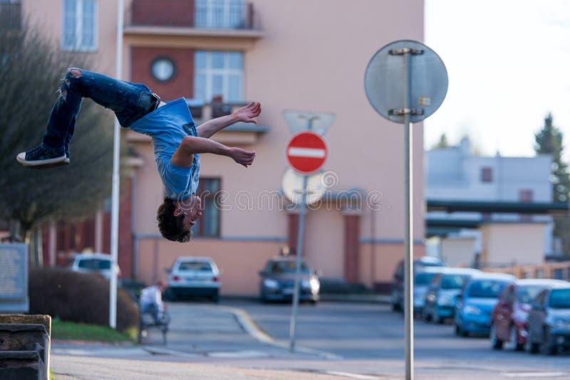 Un jeune garçon saute le saut périlleux sur la rue images stock