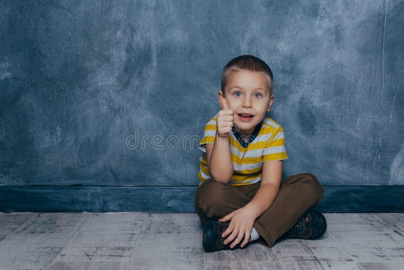 Un jeune gar?on ?motif s'assied sur un plancher en bois dans la perspective d'un mur bleu dans le studio ?motions humaines image libre de droits