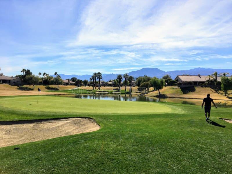 Un jeune golfeur masculin marchant vers le vert sur un pair 4 entouré par l'eau et des palmiers à l'arrière-plan sur l'oasis de d images stock