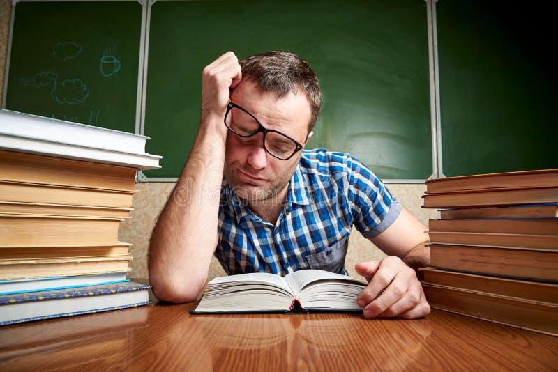 Un jeune homme épuisé avec des verres dort à une table avec des piles de livres photos stock