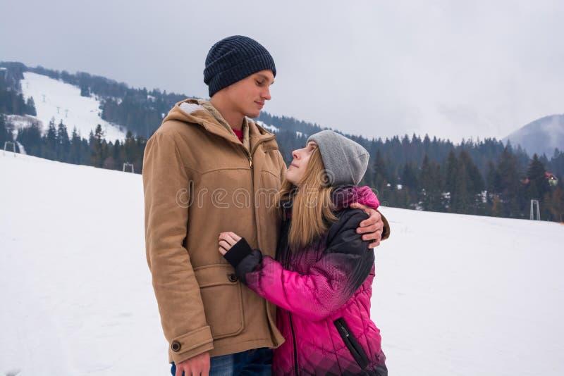 Un jeune homme étreint une fille et un regard à l'un l'autre contre un backdro image libre de droits