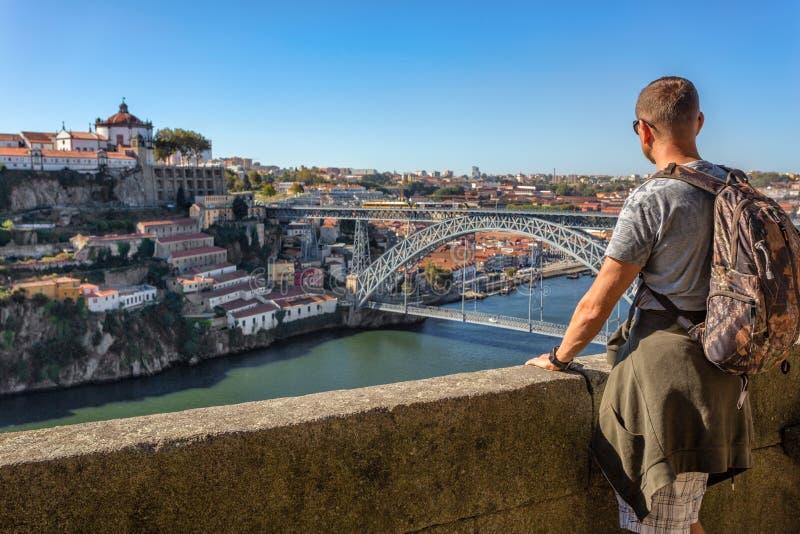 Un jeune homme admire le paysage de Porto, la rivière de Douro Vue du pont du San Luis photographie stock libre de droits