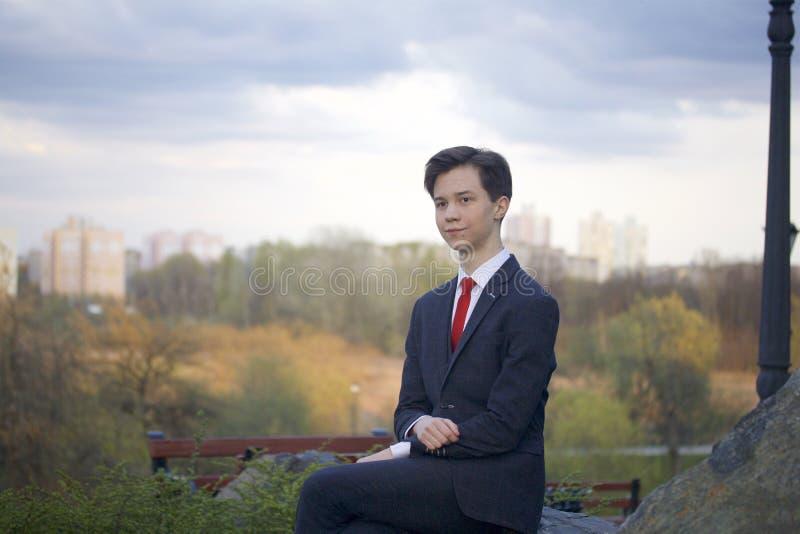 Un jeune homme, un adolescent, dans un costume classique Il s'assied sur un grand rocher en parc de ressort, ses mains étreintes  images stock