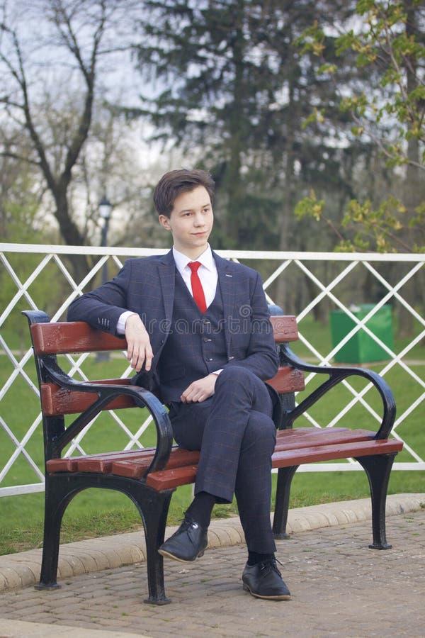 Un jeune homme, un adolescent, dans un costume classique Se repose sur un banc de vintage en parc de ressort photographie stock libre de droits