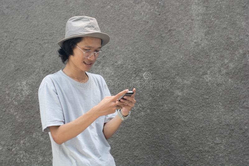 Un jeune homme asiatique attirant avec le chapeau et les verres utilisant le smarphone image stock