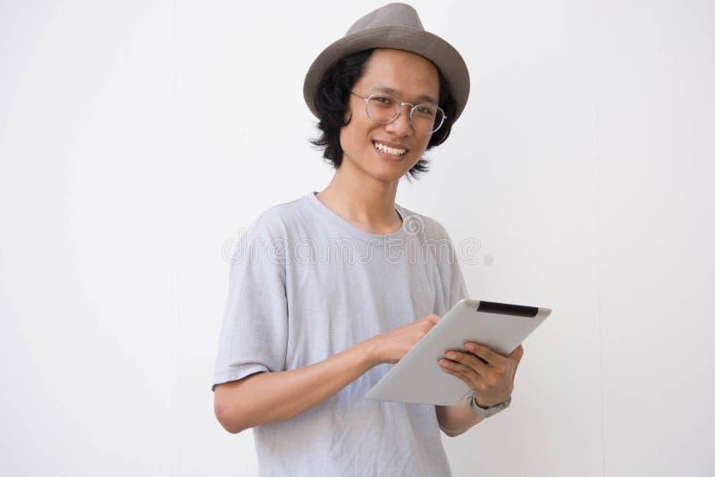 Un jeune homme asiatique avec le chapeau et les verres de chapeau feutré utilisant le comprimé et sourire à la caméra tout en ten image libre de droits