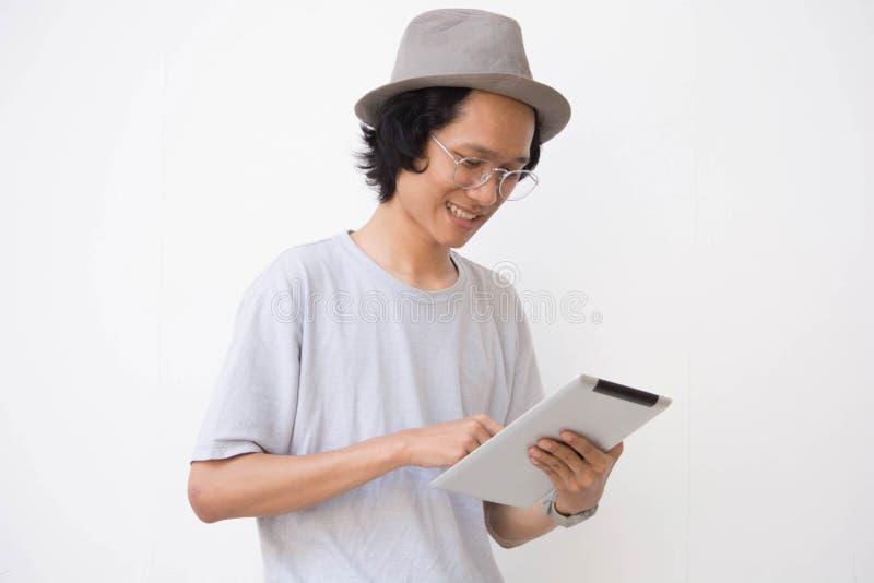 Un jeune homme asiatique avec le chapeau et les verres de chapeau feutré utilisant le comprimé et le sourire images stock
