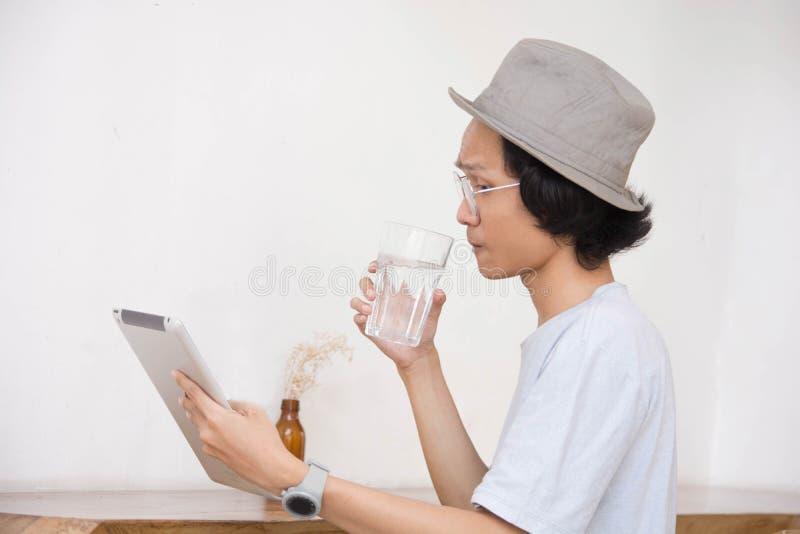 Un jeune homme asiatique avec le chapeau et les verres sourient au comprimé ou le moment d'ordinateur portable boivent un verre d photos stock