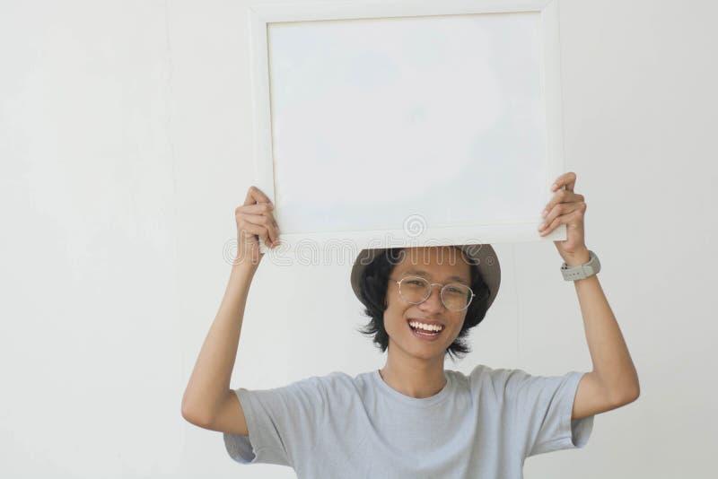 Un jeune homme asiatique avec les verres et le chapeau tenant le conseil blanc et souriant à la caméra photos libres de droits