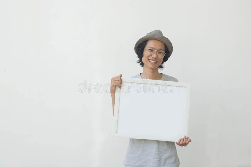 Un jeune homme asiatique avec les verres et le chapeau tenant le conseil blanc et souriant à la caméra photo stock