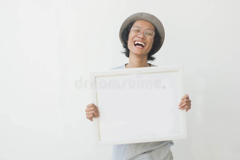 Un jeune homme asiatique heureux avec les verres et le chapeau tenant le conseil blanc et souriant à la caméra images libres de droits