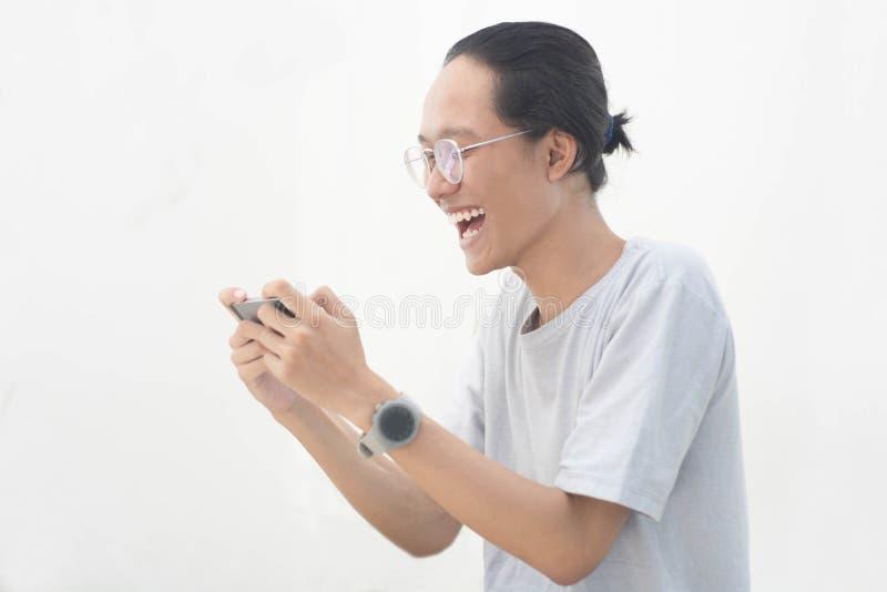 Un jeune homme asiatique utilisant le smartphone et obtenir homme asiatique enthousiaste et jeune jouant le jeu au smartphone photos stock