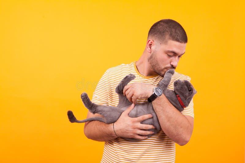 Un jeune homme attrayant tenant dans ses bras un adorable chat image stock