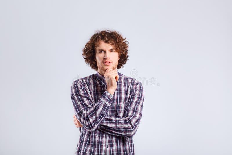 Un jeune homme aux cheveux bouclés avec une émotion réfléchie pense le lookin photos libres de droits