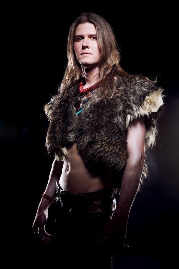 un jeune homme avec de longs cheveux et un manteau de fourrure sur son corps photographie stock