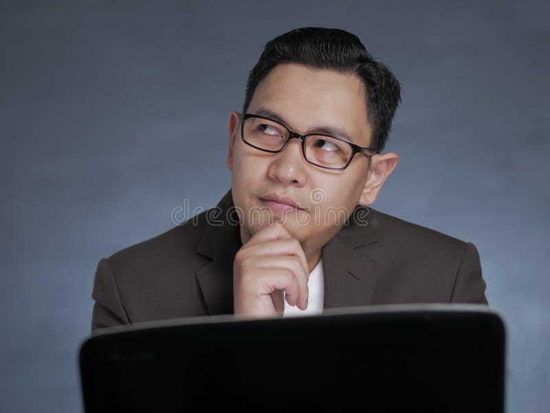 Un jeune homme avec un ordinateur portable, pensant sérieusement photographie stock libre de droits