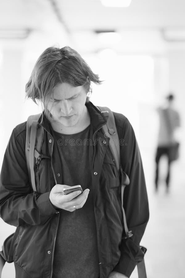 Un jeune homme avec un téléphone portable à disposition photos stock