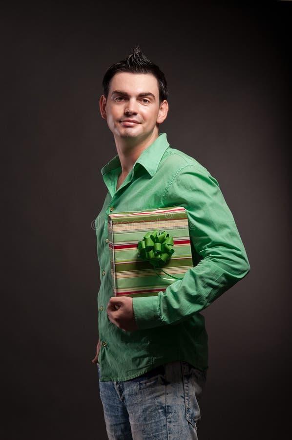 Un jeune homme avec un cadeau dans les mains photographie stock