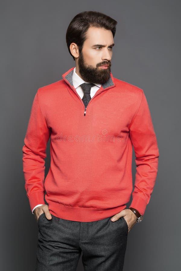 un jeune homme avec une barbe et un débardeur et pantalons, se tenant image libre de droits
