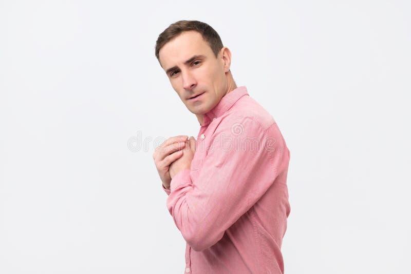 Un jeune homme avide dans la chemise rose cache quelque chose dans des ses mains photos stock