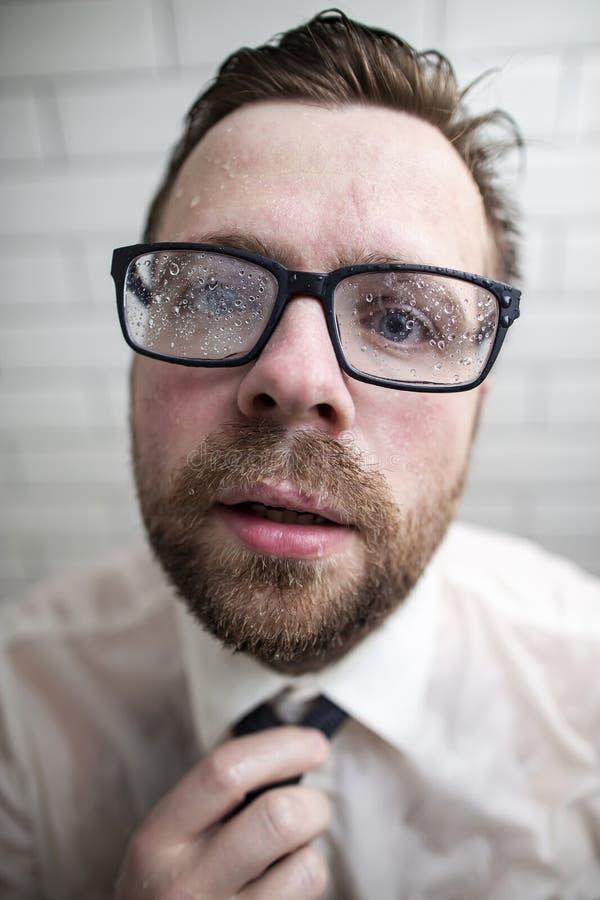 Un jeune homme barbu avec une expression étrange sur son visage, sueur photos stock