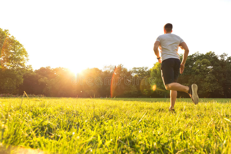 Un jeune homme beau courant pendant le coucher du soleil en parc photo libre de droits
