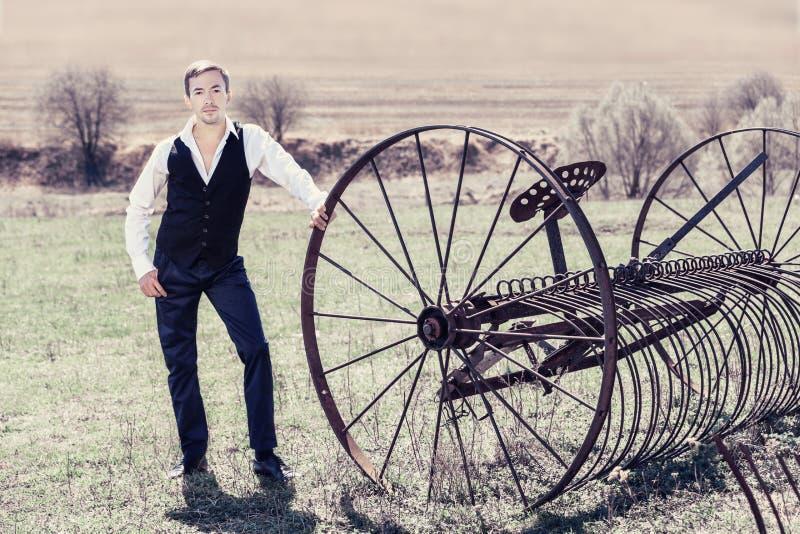 Un jeune homme beau dans un gilet, des pantalons noirs et une chemise blanche se tient à côté d'une machine de fenaison dans le d images libres de droits