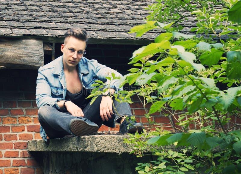 Un jeune homme beau s'asseyant sur le toit images libres de droits