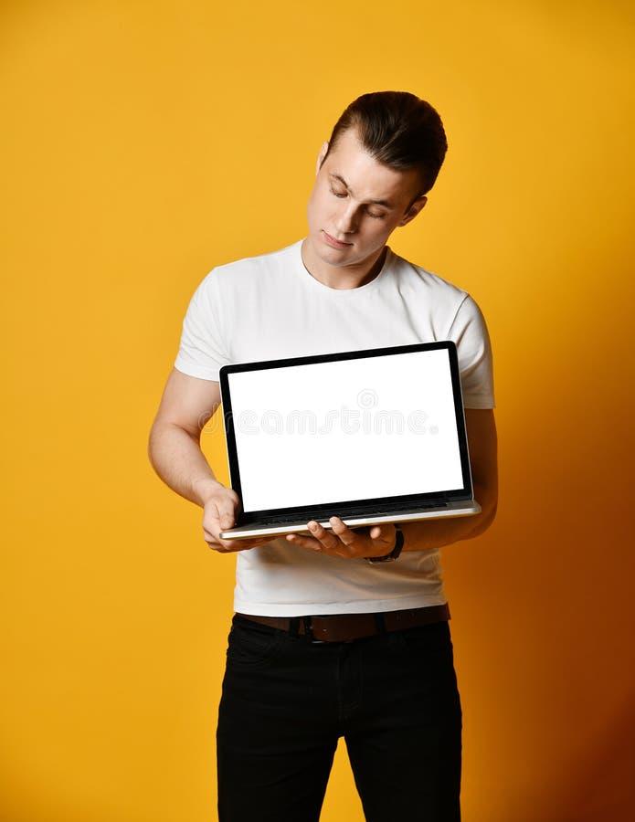 Un jeune homme beau tenant et montrant l'écran d'un ordinateur portable photo libre de droits