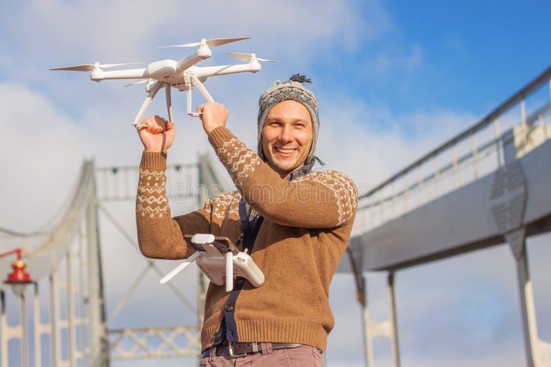 Un jeune homme bel d'aspect européen lance un bourdon à l'arrière-plan d'un ciel bleu sur un pont en hiver photos libres de droits