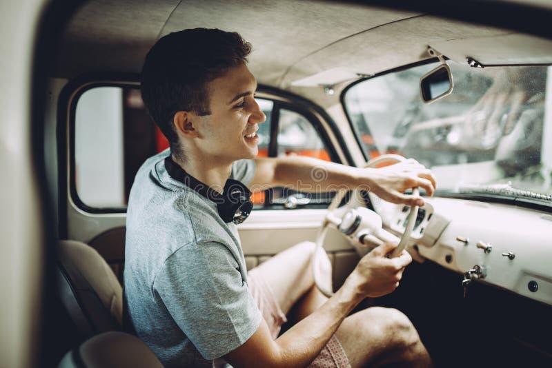 Un jeune homme blond gare sa voiture de ventage photos stock