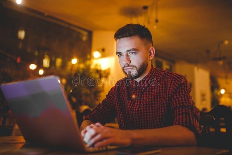 Un jeune homme caucasien bel avec la barbe et le sourire toothy dans une chemise à carreaux rouge travaille derrière un ordinateu photos libres de droits