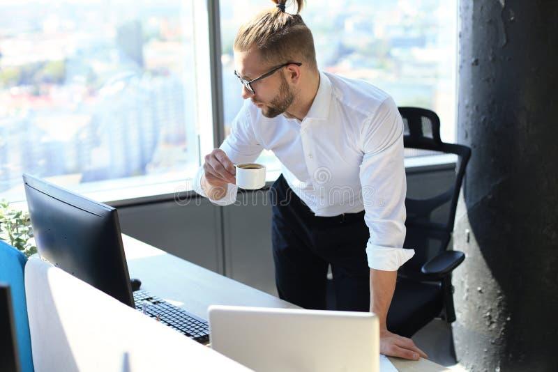 Un jeune homme confiant qui travaille sur son ordinateur portable et boit de la tasse de café pendant qu'il est assis au bureau image stock