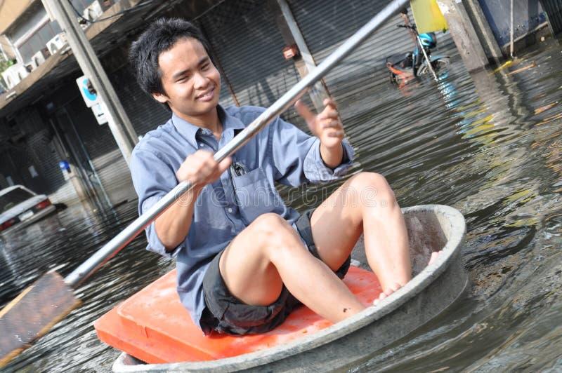 Un jeune homme continue à sourire pendant qu'il rame son bateau dans une rue inondée de Bangkok, Thaïlande sur la 11ème de novemb image stock